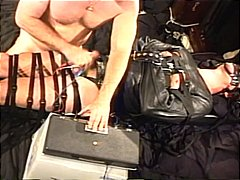 Downright tied hunk in leather strait-jacket in cbt with high voltage stim to testicles as he's drained off