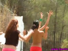 Several youthful sweethearts play outdoors half-nude displaying off their hooters